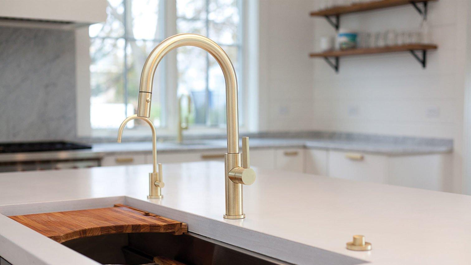 Corsano kitchen ensemble in satin brass on white marble counter