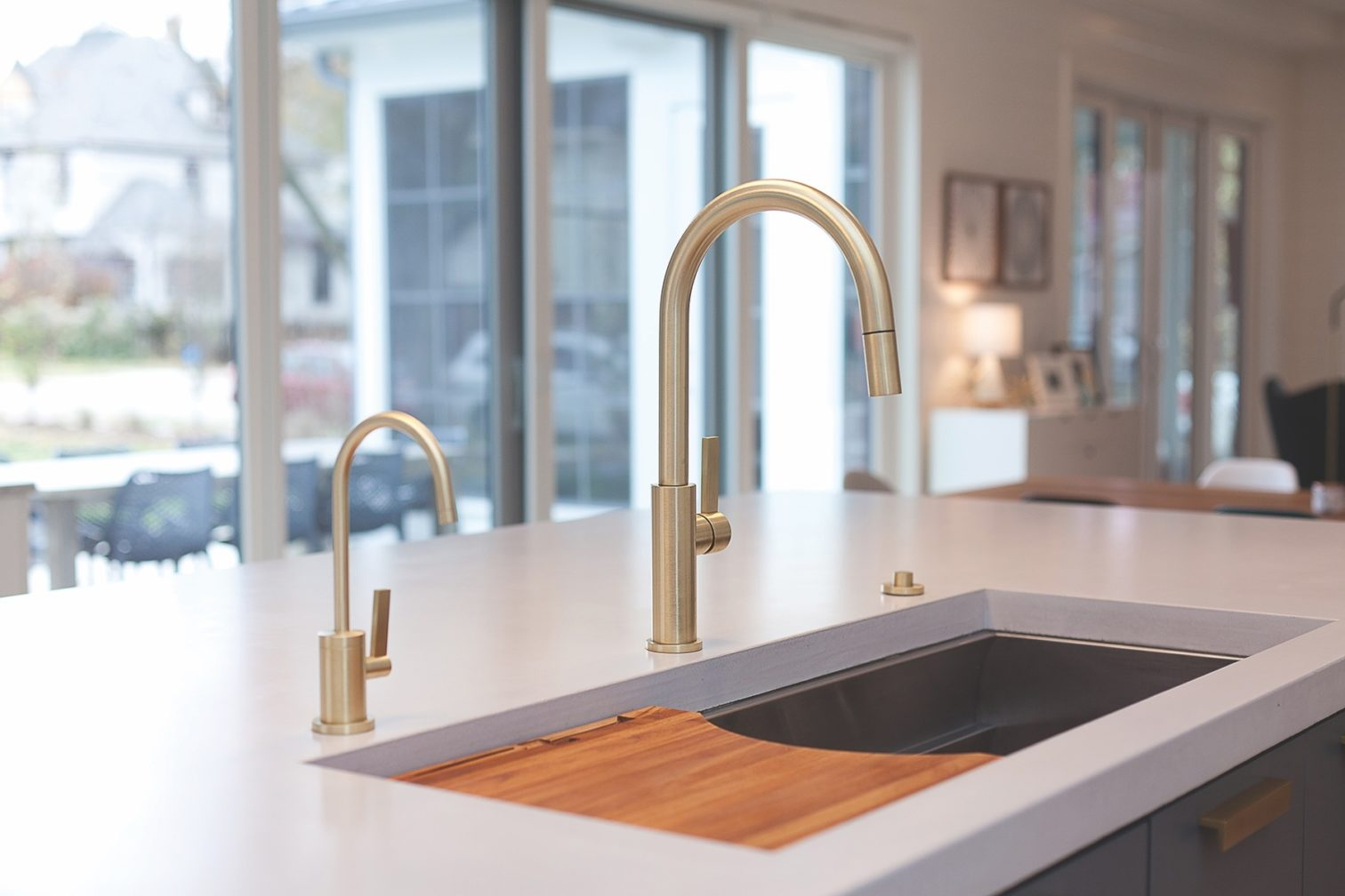 Corsano pull-down kitchen faucet in brass with accessories on sink