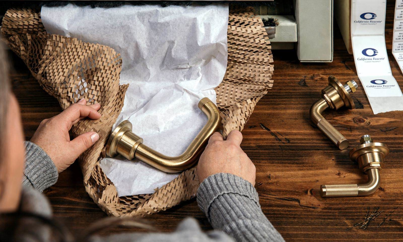 person wraps faucet in eco-friendly recyclable packaging
